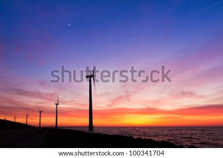 Windmill landscape sunset moon - stock photo