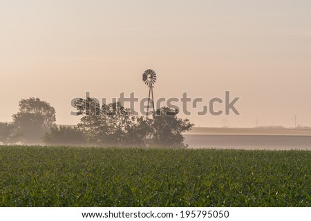 Windmill on a foggy morning - stock photo