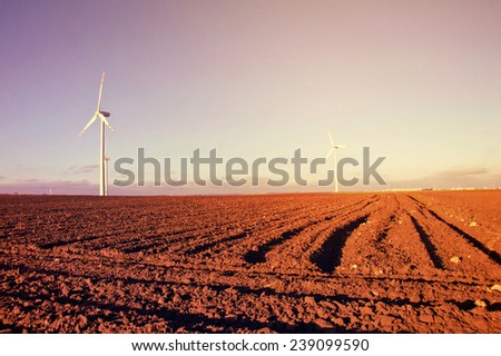 Windmill on the plowed field. Vintage sunburst picture. Alternative energy. - stock photo