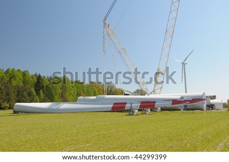Windmill power generator components on the green field under blue sky. Windmil construction. - stock photo