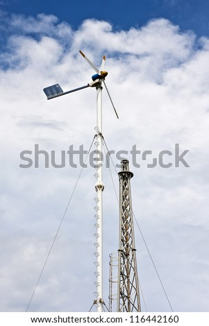 Windmill producing alternative energy with a cloudy sky - stock photo