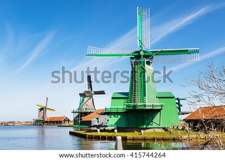 Windmill row in Zaanse Schans, traditional village in Netherlands, North Holland against blue cloudy sky - stock photo