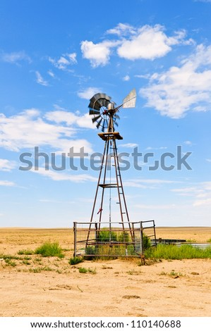 Windmill water pump to supply livestock with drinking water. - stock photo
