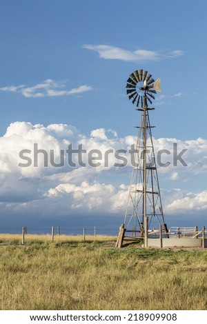 windmill with a pump and cattle water tank in shortgrass prairie against stormy sky, Pawnee National Grassland in Colorado near Grover - stock photo