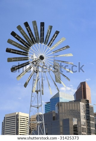 windmill with modern office towers - stock photo