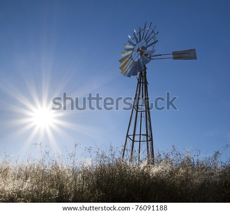 Windmill with sun rising blue sky