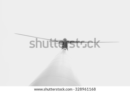 Windmill with three blades view from below. Eolic energy. Closeup and  black and white photography.  - stock photo