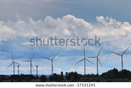 windmills against a cloudy sky - stock photo