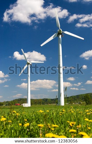 Windmills against blue sky with white clouds and yellow flowers on the ground - stock photo