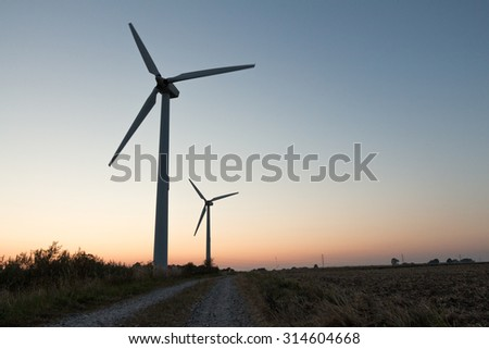 windmills and a pathway. can be used for windmills, energy, nature, climate and environment themes - stock photo