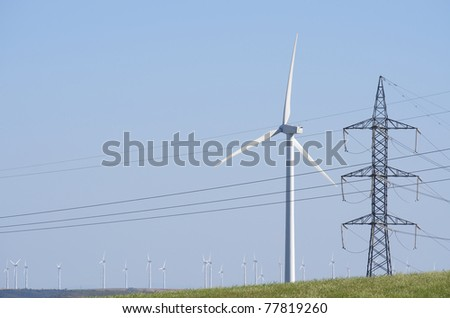 windmills and power line with blue and clear sky - stock photo