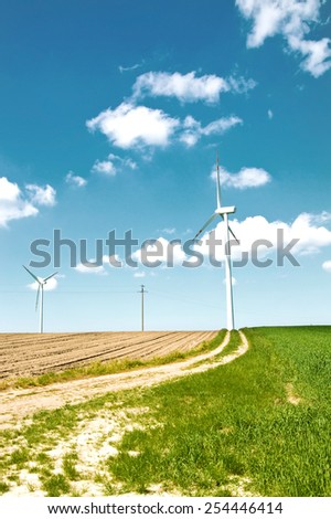 Windmills. Clean renevable energy conceptual image. Windmills on the field at summer.  - stock photo