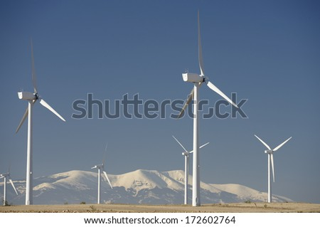 Windmills for renewable electric energy production, at background is Moncayo Peak, Pozuelo de Aragon, Zaragoza, Aragon, Spain