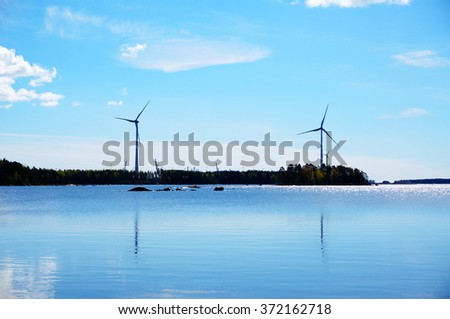 Windmills for renewable electric energy production at coast with blue sky background, Finland - stock photo