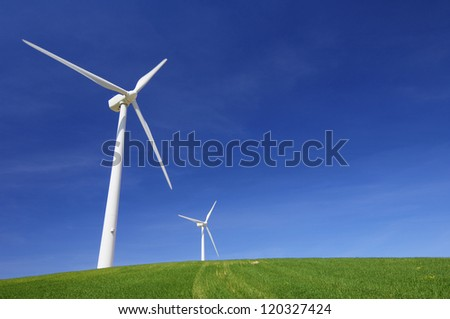 windmills for renewable energy production in a meadow of fresh grass - stock photo