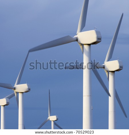 windmills group for energy production with cloudy sky - stock photo