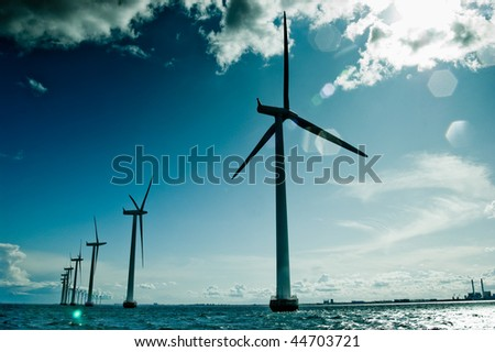 Windmills in a row against sun - stock photo
