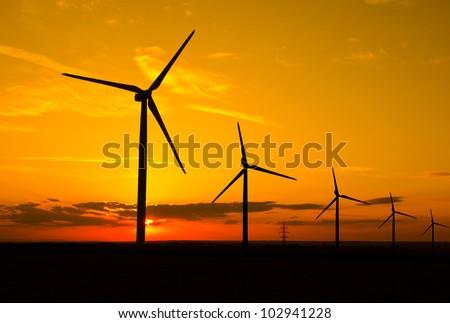 Windmills in sunset - stock photo