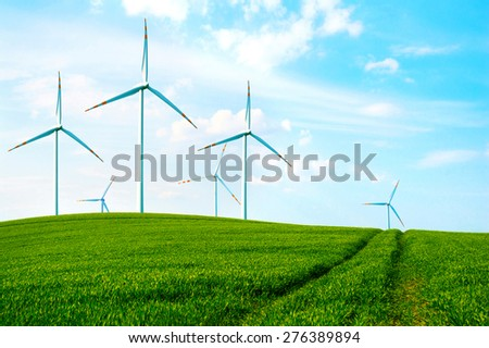 Windmills in the countryside filed with green fresh grass at summer. - stock photo