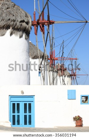 Windmills on a hillside near the sea in Mykonos Island, Greece - stock photo