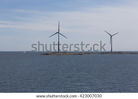 Windmills on an island in the middle of the sea.