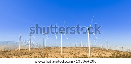Windmills On Hill With Mountains in The Background - stock photo