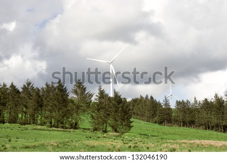 windmills on the hills of Glenough in county Tipperary Ireland with trees and fields in foreground - stock photo