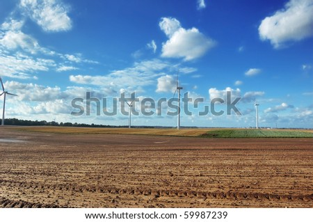 Windmills on the plowed field. - stock photo