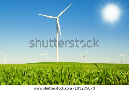 Windmills to generate wind power with blue sky and green meadow