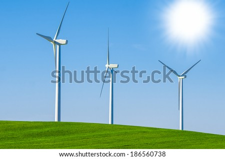 Windmills to generate wind power with blue sky and green meadow - stock photo