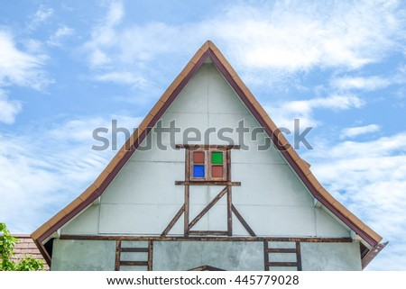 Window and house roof  against blue sky.