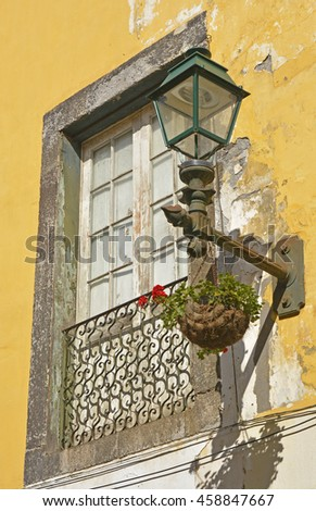 Window and lamp on house in side street of Funchal, Madeira, Portugal. With peeling paintwork