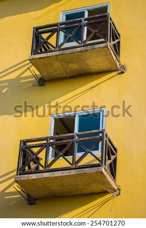Window balcony in the yellow wall - stock photo