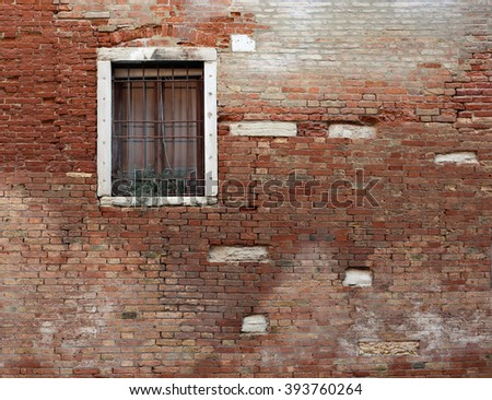 Window, brick wall of an old house next to the canal