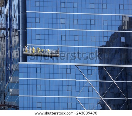 Window cleaner and maintenance on the outside of a skyscraper - stock photo