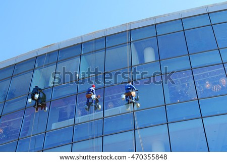 window cleaner on the background of the Windows of the building
