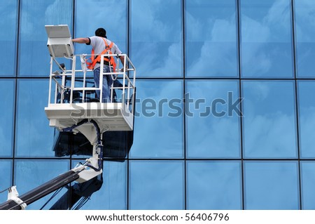 Window cleaner working on a glass facade in a gondola - stock photo