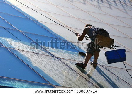 Window cleaner works on high rise building.Window cleaning is considered one of the most dangerous job in the world. - stock photo