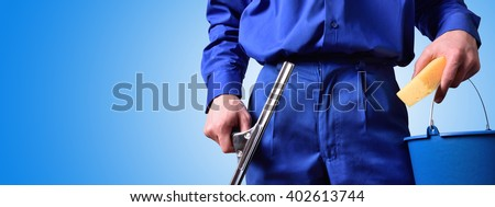 Window cleaning employee with work tools and blue background. Background and concept. horizontal composition. - stock photo