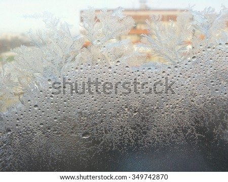 Window glass covered in frost. Condensation leaves little drops of water on the glass which then freeze and form complicated patterns. New Year and Christmas winter background.