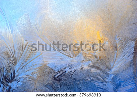 Window glass covered with ice pattern against sunset