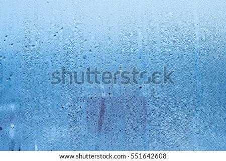 Window glass with condensation, strong, high humidity in the room, large water droplets flow down the window, cold tone, natural water drops on window glass