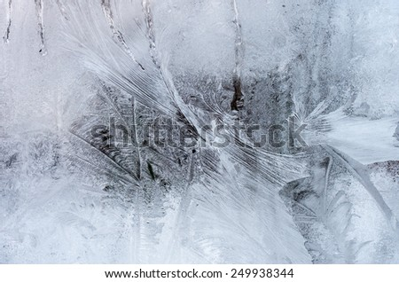 Window glass with hoarfrost drawings, taken from inside on the building in cold winter weather - abstract winter background