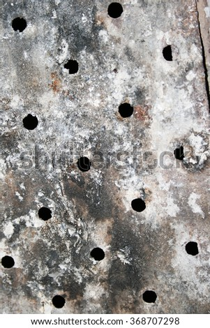 window grating from old rusty iron on a stone wall of ancient prison or a dungeon - stock photo