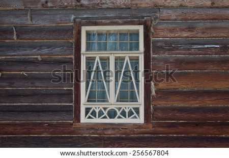 Window in a white frame on an old wooden wall. - stock photo