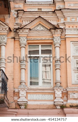 Window in an old classical building on street with column