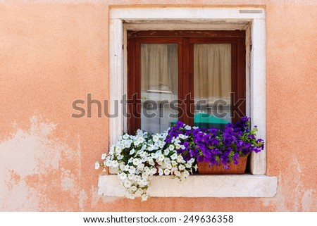 Window in an old house decorated with flower pots and flowers