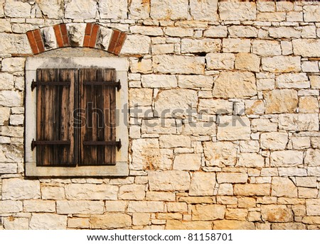 Window in the old stone wall - stock photo