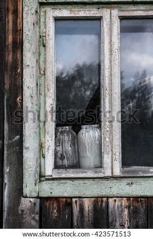 Window of an old wooden house with peeling paint and milk bottles inside