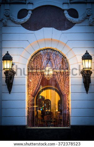 WIndow of cafe in Budapest, Hungary, Europe. Christmas decorations and lights. Two big street lamps on sides of window. Cozy and warm interior of restaurant.